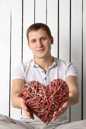 Man with hand-made reg wooden heart sitting near the wall