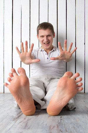 Smiling man shows fingers while sitting near the wall