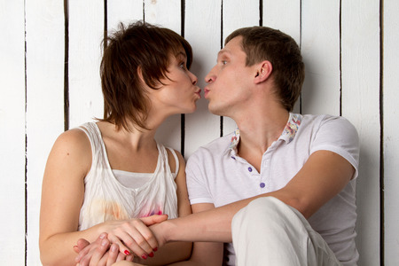 Young couple is kissing near the white wall
