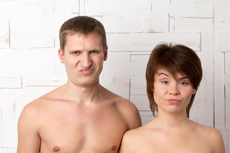 dissatisfaction: Young couple with emotions of dissatisfaction near the white wooden wall