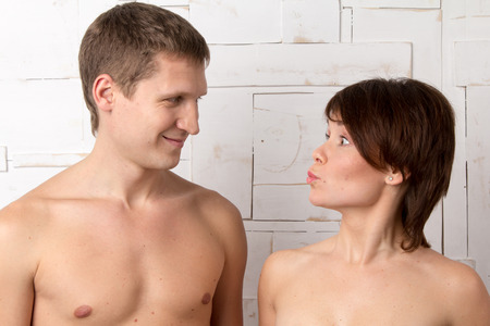 suddenness: Young couple with emotions of suddenness near the white wooden wall Stock Photo
