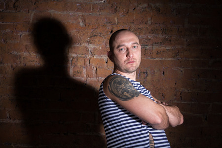 Serious bald man standing near the brick wall