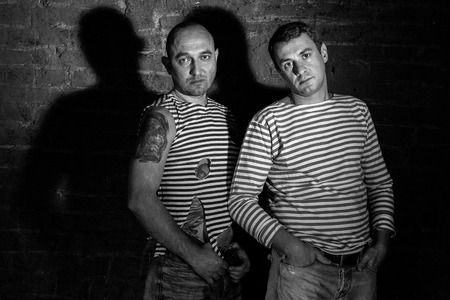 Two serious men standing near the wall in black-and-white