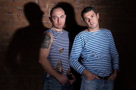Two men standing near the brick wall