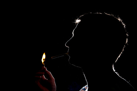 Silhouette of man who lights the cigarette