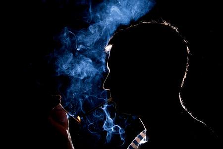 Silhouette di uomo che accende la sigaretta Archivio Fotografico - 36058378