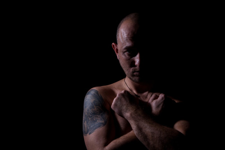 Silhouette of man with crossed hands and tattoo photo