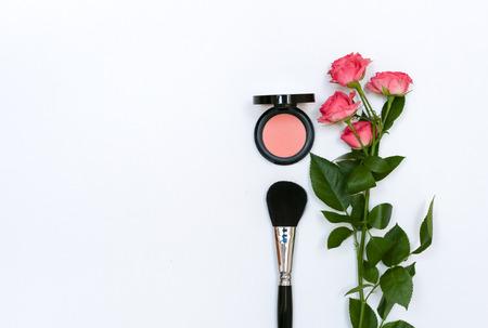 Composizione decorativa con cosmetici trucco, spazzole, shadoes e fiori. Vista dall'alto su sfondo bianco Archivio Fotografico - 60627340