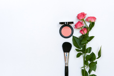 Decorative composition with makeup cosmetics, brushes, shadoes and flowers. Top view on white background Archivio Fotografico