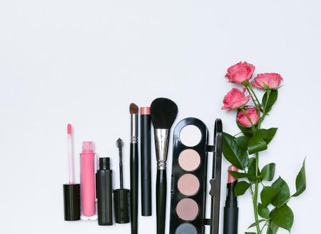 Composizione decorativa con cosmetici trucco, spazzole, shadoes e fiori. Vista dall'alto su sfondo bianco Archivio Fotografico - 60627342