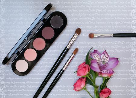 Composizione decorativa con cosmetici trucco, pennelli, shadoes e fiori. Vista dall'alto su sfondo grigio Archivio Fotografico - 60627377