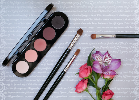 Decorative composition with makeup cosmetics, brushes, shadoes and flowers. Top view on grey background Archivio Fotografico
