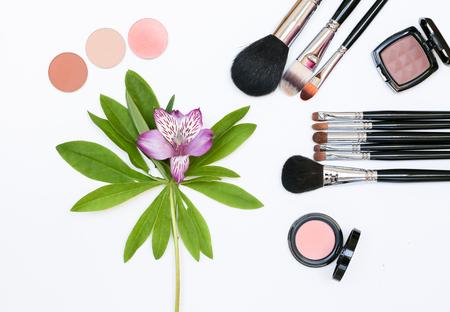 Composizione decorativa con cosmetici trucco, pennelli, shadoes e fiori. Vista dall'alto su sfondo bianco Archivio Fotografico - 60621185