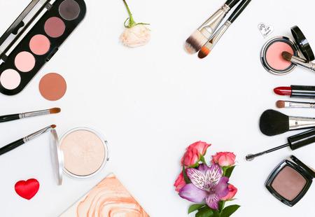 Composizione decorativa con cosmetici trucco, pennelli, shadoes e fiori. Vista dall'alto su sfondo bianco Archivio Fotografico - 60621187