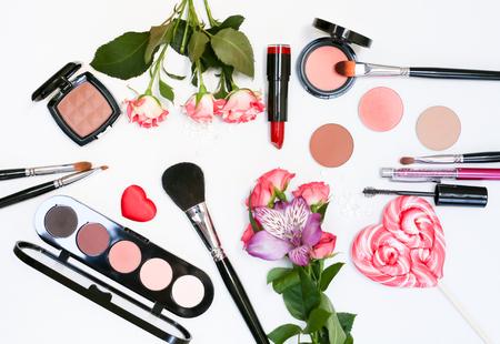 Composizione decorativa con cosmetici trucco, pennelli, shadoes e fiori. Vista dall'alto su sfondo bianco Archivio Fotografico - 60621189