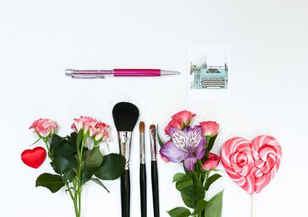 Composizione con cosmetici trucco, penna, carta e fiori. Vista dall'alto su sfondo bianco Archivio Fotografico - 60621190