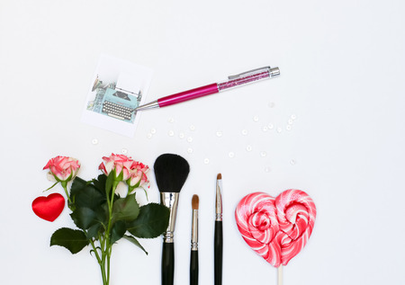 Composition with makeup cosmetics, pen, card and flowers. Top view on white background