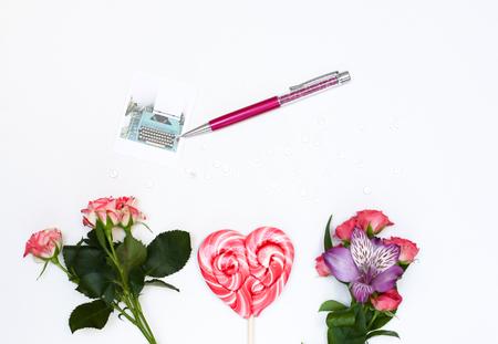 Composizione con cosmetici trucco, penna, carta e fiori. Vista dall'alto su sfondo bianco Archivio Fotografico - 60605241
