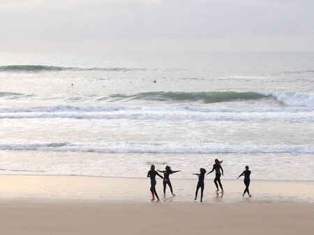 surfer people carrying surfboard on an ocean beach in Portugal Archivio Fotografico - 139872426