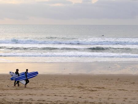 surfer people carrying surfboard on an ocean beach in Portugal