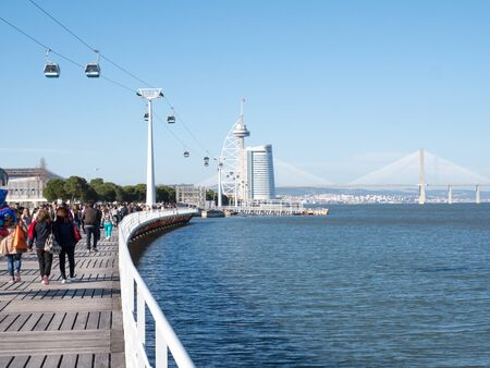 People wakling on a seafront parapet and looking to a sea and bridge Archivio Fotografico - 139872414
