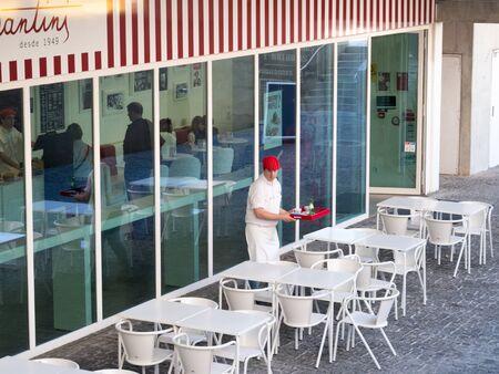 Visitors and waiter in the Portuguese cafe Archivio Fotografico - 139872411