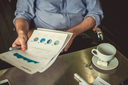 transmitting: View of businessman sitting at the table with cap of tea , transmitting a piece of paper with charts