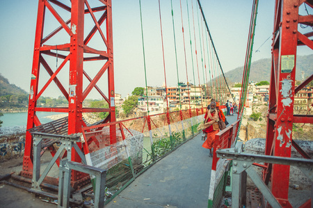 Rishikesh. India. April 13, 2017. Pilgrims walk through the suspension bridge