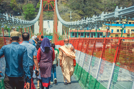 Rishikesh. India. April 13, 2017. People walk on the suspension bridge Ram Jhula.