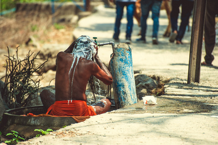 washed: Sadhu is washed under running water near the road.