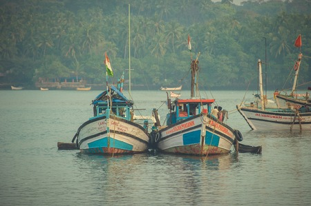 boatman: India, Goa - February 2, 2017: Fishing boats with Indian flags stand on the dock.