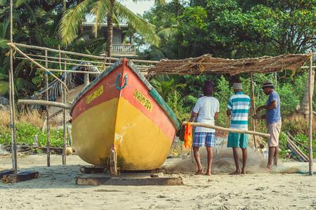 trawler net: India, Goa - November 19, 2016 Fishermen weave nets near a yellow boat. Editorial