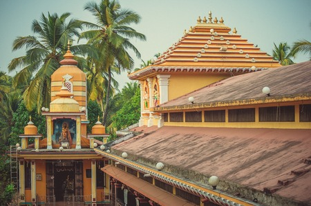 A colorful Hindu temple against a backdrop of palm trees in Goa. Stock Photo