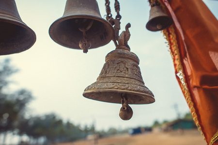 Bell with ornament on the background of trees.