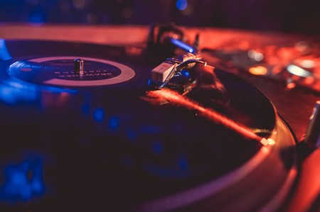 Vinyl record on the turntable in the music club in the light of blue and red light. Stock Photo