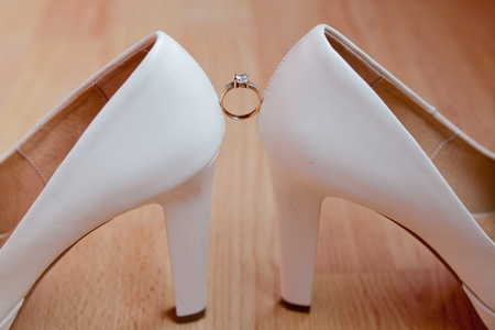 wedding ring between wedding shoes on a parquet background