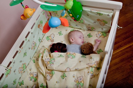 New born child in wooden co-sleeper crib. Infant sleeping in bedside bassinet. Safe co-sleeping in a bed side cot. Little boy taking a nap under knitted blanket. Top view.