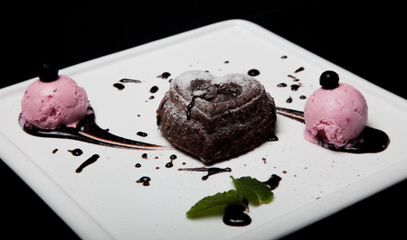 Dessert fondan chocolate with ice-cream on a white plate on a black background. Exquisite French chocolate dessert fondan. Stock Photo