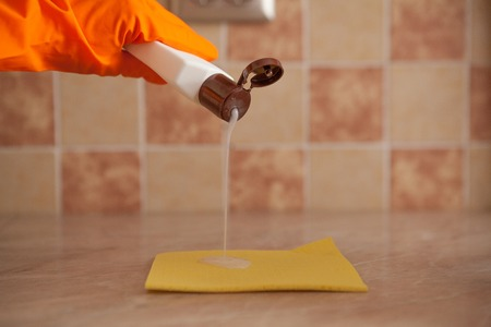Woman hand holding yellow sponge and pouring cleaning liquid on it. housekeeping and hygiene concept.