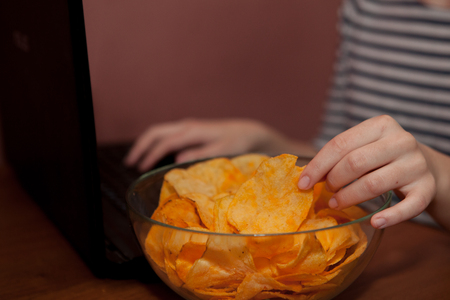 Young happy woman eating chips near a computer. Unhealthy concept.