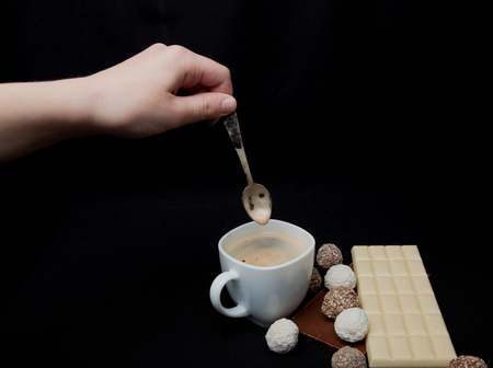 Woman adding sugar in coffee in cafe. Cofe, Stack of Black and White Chocolate isolated on black background, place for text.