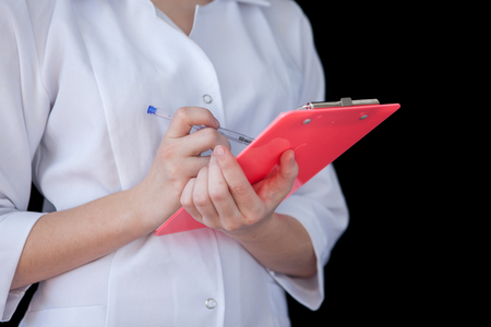 Front view of a young intellectual healthcare doctor in labcoat on black backround. Doctor with a notebook in his hands with free space for text.