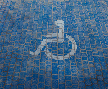 Top view on parking sign for disable people. Disabled parking space and wheelchair symbols on pavement.
