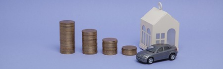 Gray machine model and home with coins in the form of a histogram on a purple background. Concept of lending, savings, sale, lease of property. Stock Photo