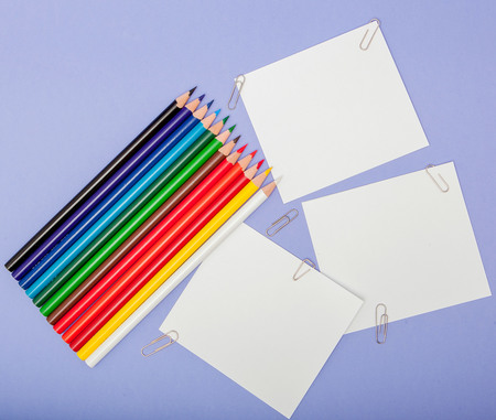 Blanks sheet of papers and color pencils on violet background for Projects and Announcements.