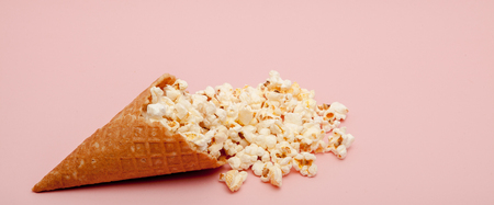 Popcorn in ice cream cones on pink background. Stock fotó
