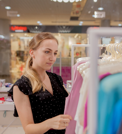 The woman looks at the on clothes. Advertise, Sale, Fashion concept. Woman standing in shop, looking hangers with clothes, choosing new clothes in shop.