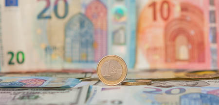 Financial dominance: One Euro in a vice against the background of the American Dollar and Euro with space for text. Stock Photo