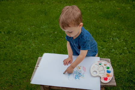 Cute little boy painting with a paint hands using gauche paints.