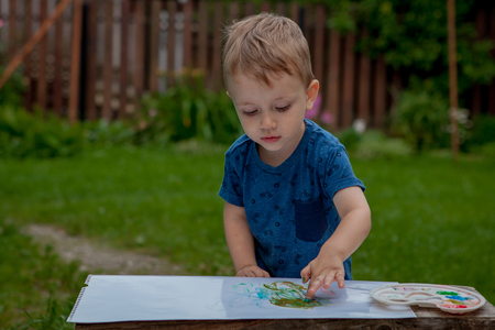 Cute little boy painting with a paint hands using gauche paints. Banque d'images